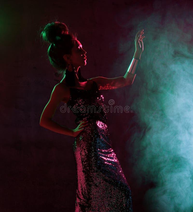 Härlig modebrunettkvinna som poserar i blått och rosa neonljus i guld- gnistrandeklänning för mode på mörker royaltyfri bild