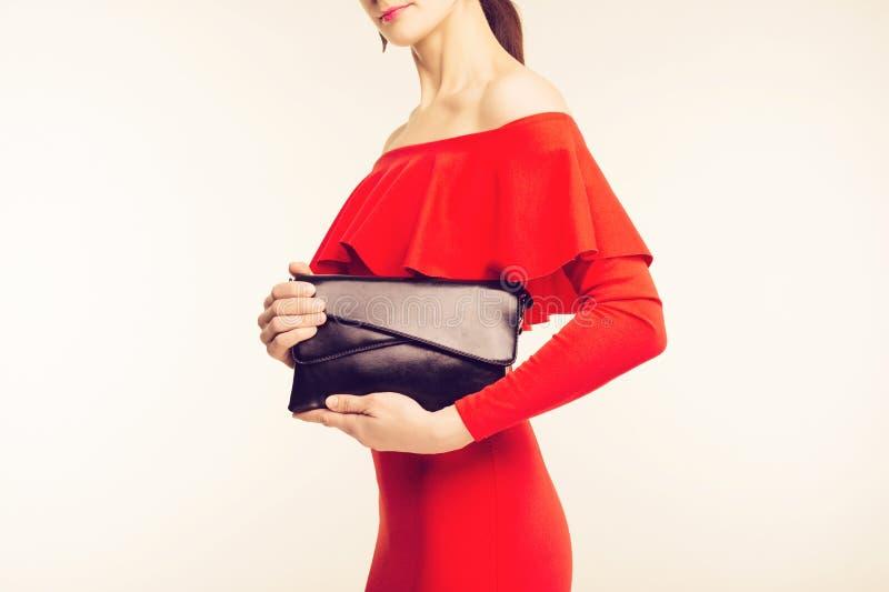 Härlig modedräkt, röd klänning och svart stor läderpåse i hand av flickan Stilfull tillbehör royaltyfri foto