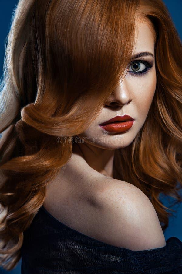 Härlig modeflicka med långt krabbt rött brunt hår blond modell med den lockiga frisyren och trendig rökig makeup royaltyfri bild