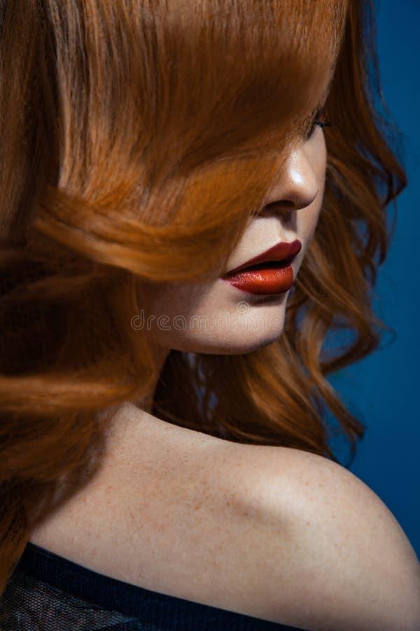Härlig modeflicka med långt krabbt rött brunt hår blond modell med den lockiga frisyren och trendig rökig makeup arkivbild