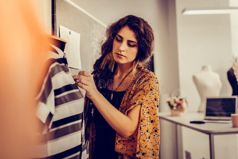 Härlig modeformgivare som utgör en klänning arkivbild