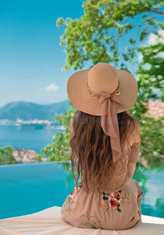 Härlig modekvinna i strandhatt som tycker om havssikt vid swimmi fotografering för bildbyråer