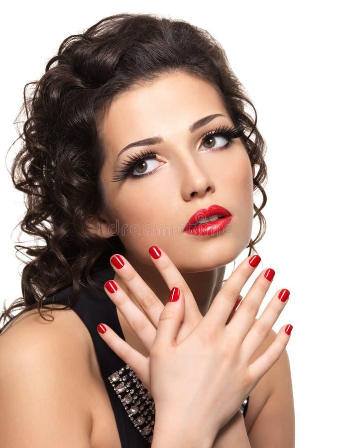 Härlig modekvinna med den röda manicuren och kanter royaltyfri bild