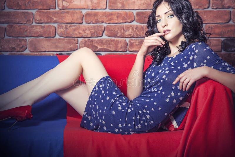 Härlig modell för kvinna på soffan i klänningen i blå och röd t arkivfoto