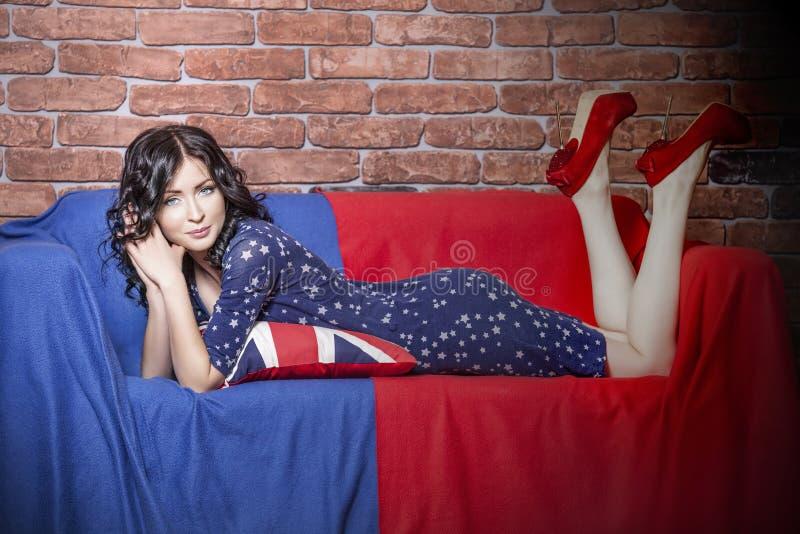 Härlig modell för kvinna på soffan i klänningen i blå och röd t arkivbilder