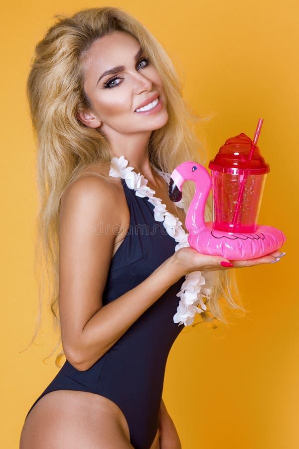Härlig modell i en bikini och solglasögon och att rymma en drink och en uppblåsbar rosa flamingo royaltyfria foton
