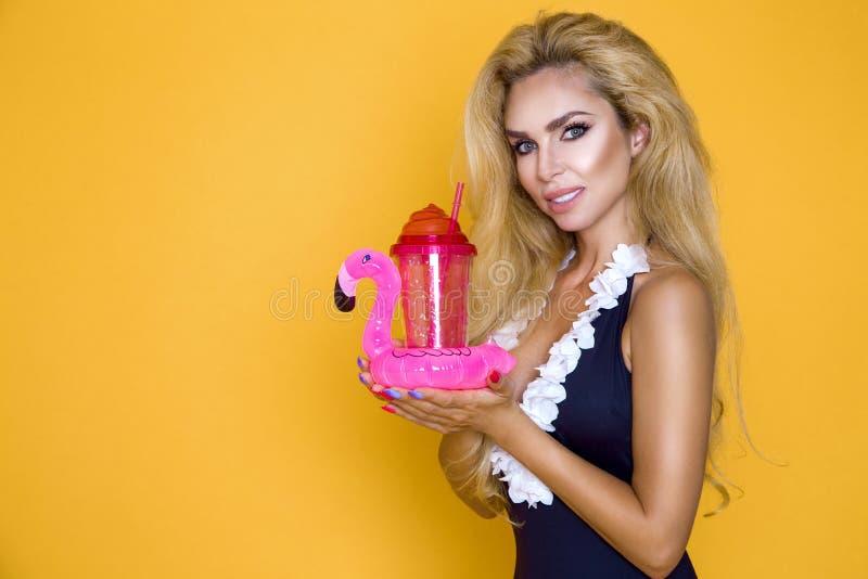 Härlig modell i en bikini och solglasögon och att rymma en drink och en uppblåsbar rosa flamingo royaltyfri foto