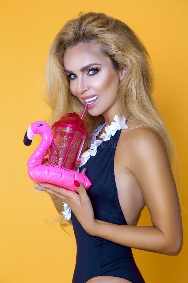Härlig modell i en bikini och solglasögon och att rymma en drink och en uppblåsbar rosa flamingo arkivfoto