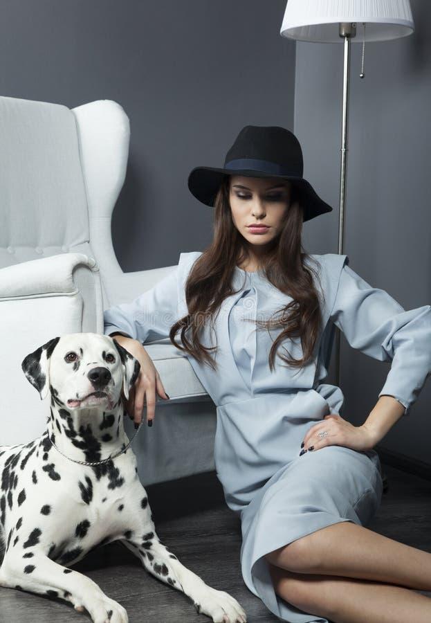 Härlig modell i en hatt med härlig makeup och en dalmatian hund arkivfoto