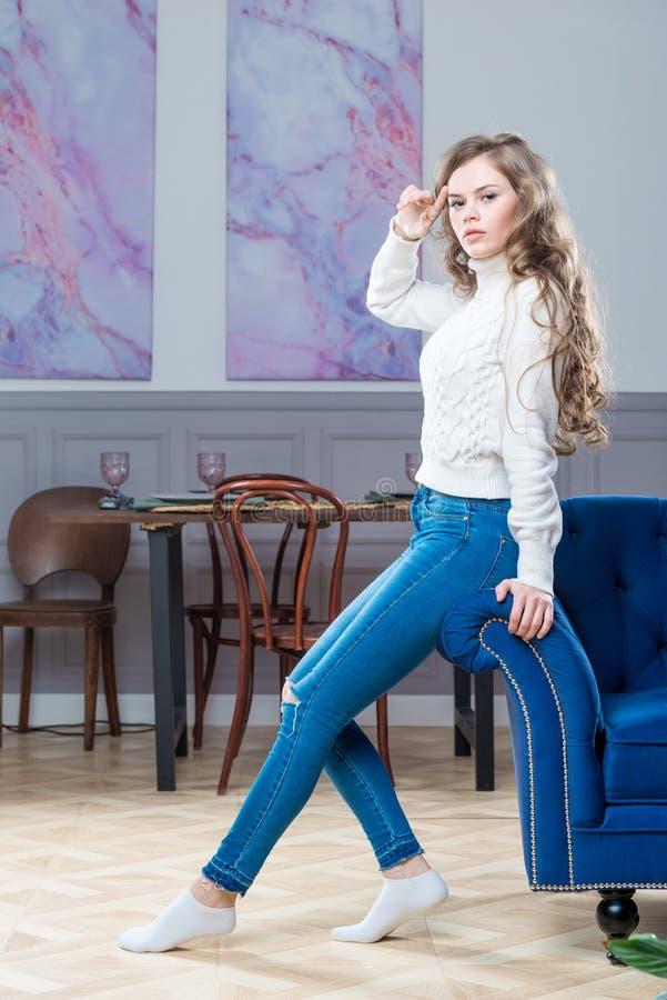 Härlig modell i en tröja och jeans i vardagsrummet på royaltyfri bild