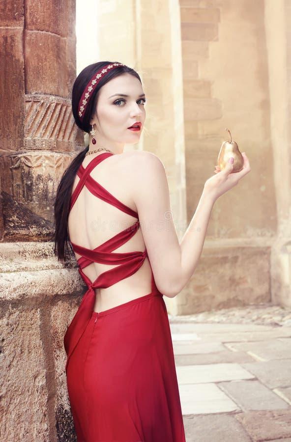 Härlig modell i röd klänning och smycken fotografering för bildbyråer