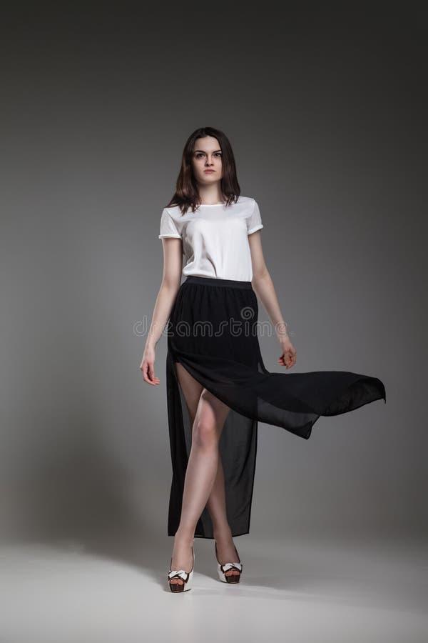 Härlig modell i vitöverkanten och den svarta kjolen som poserar på grå bakgrund arkivbilder