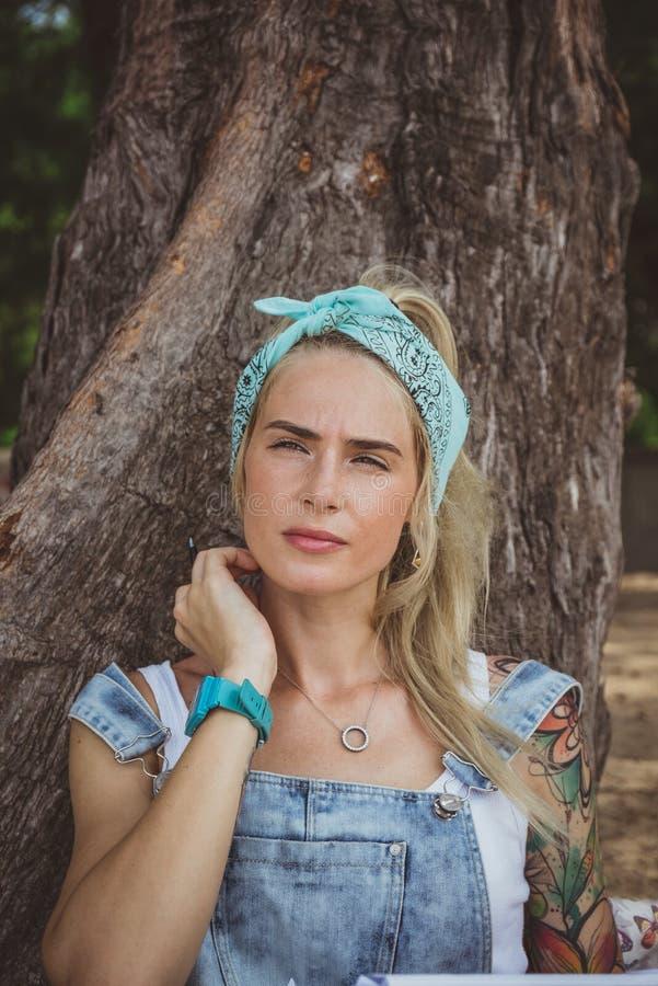 Härlig modell med tatueringar som sitter på stranden nära ett träd Bär en turkosbandana En modern kvinna Vila in royaltyfri bild