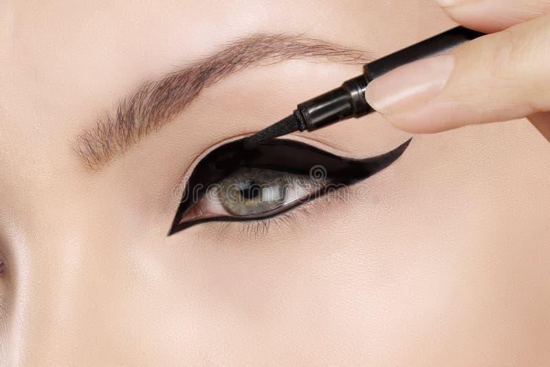 Härlig modell som applicerar eyelinercloseupen på öga royaltyfri bild