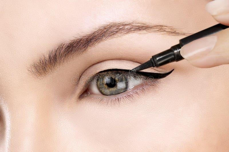 Härlig modell som applicerar eyelinercloseupen på öga royaltyfria bilder