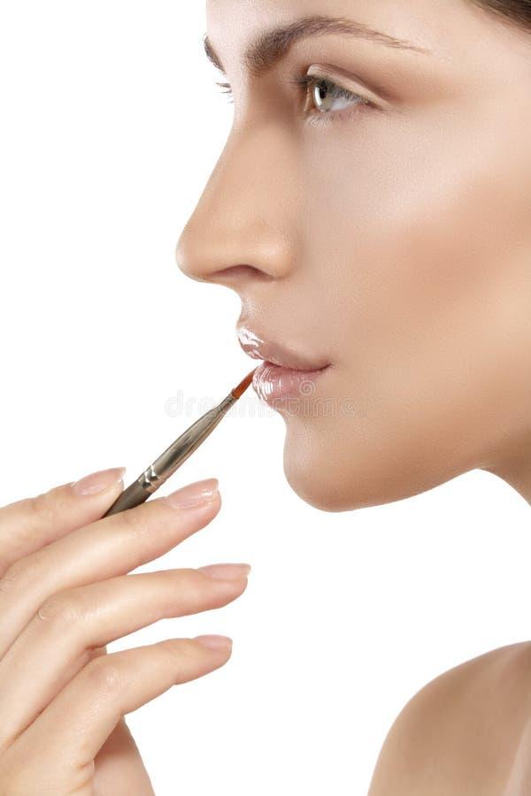 Härlig modell som applicerar kantglans med en borste royaltyfri fotografi