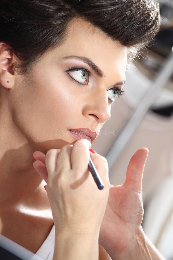 Härlig modell som har kanteyeliner att appliceras av makeupkonstnären arkivfoton
