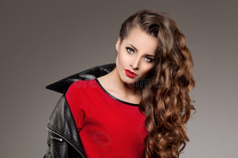 Härlig modellbrunett för ung kvinna med långt krullat hår med arkivfoto