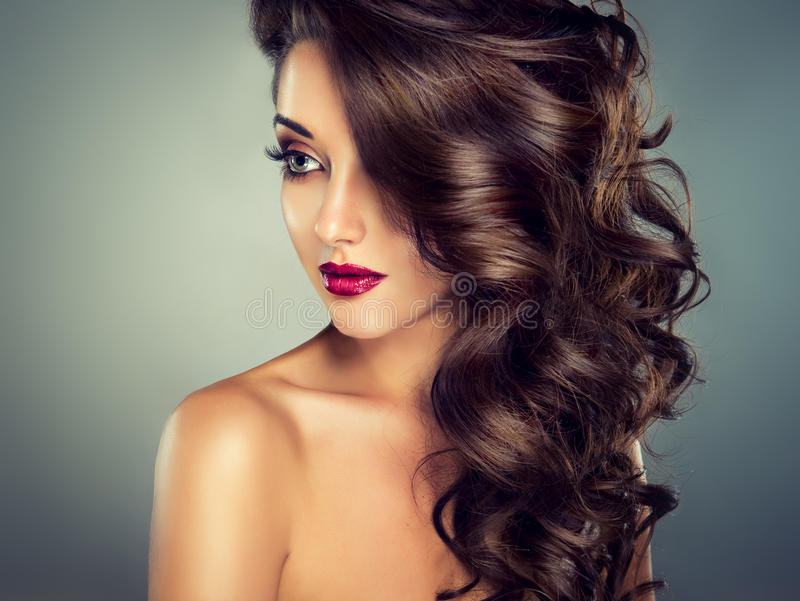 Härlig modellbrunett med långt krullat hår arkivbilder
