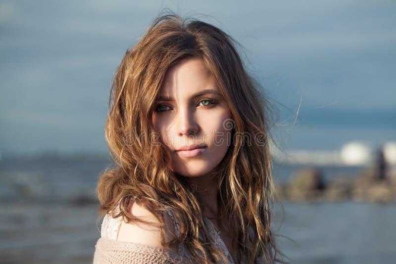 Härlig modellflicka med lockigt hår på havkusten, romantisk skönhetstående royaltyfri fotografi