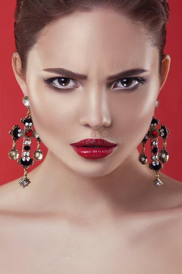 Härlig modellflicka på en röd bakgrund Skönheten av en kvinna arkivfoton