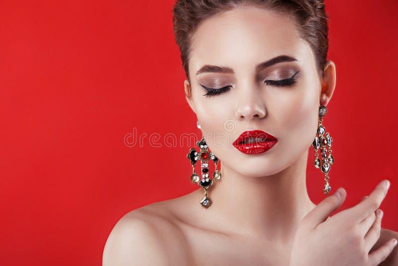 Härlig modellflicka på en röd bakgrund Skönheten av en kvinna royaltyfri bild
