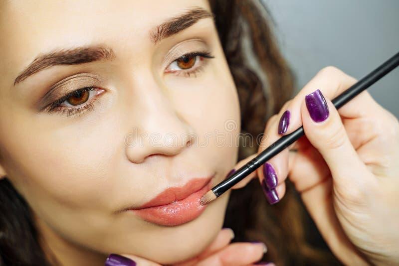 Härlig modellflicka som applicerar lipgloss läppstift applicera glanskanten gör upp professionelln royaltyfria bilder