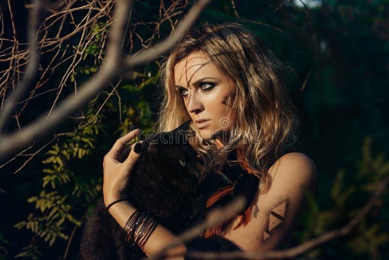 Härlig modellstående för ung kvinna med den svarta katten i skog w fotografering för bildbyråer