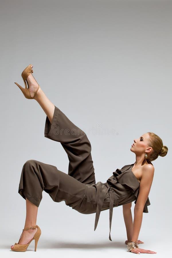 Härlig modemodell i höga häl som sparkar luften. arkivfoto