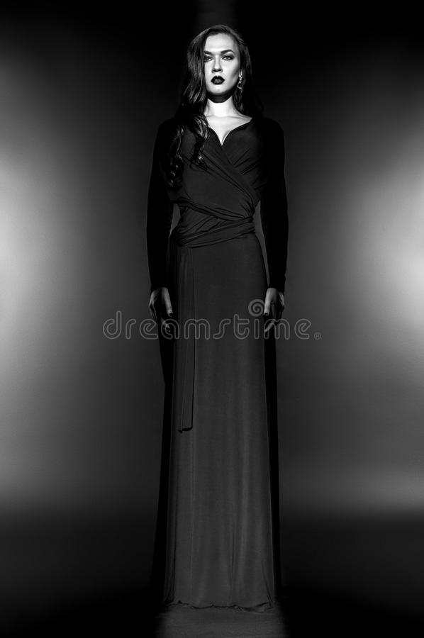 Härlig modemodell i svart klänning i studio arkivfoton