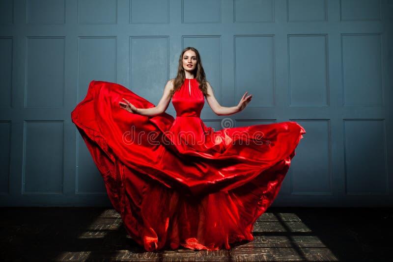 Härlig modemodell Woman i röd silkeslen klänning arkivfoto