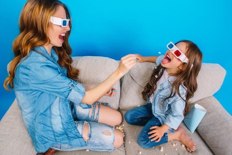 Härlig moder för lyckliga söta ögonblick med långt brunetthår som har gyckel med dottern på soffan på blå bakgrund arkivfoto