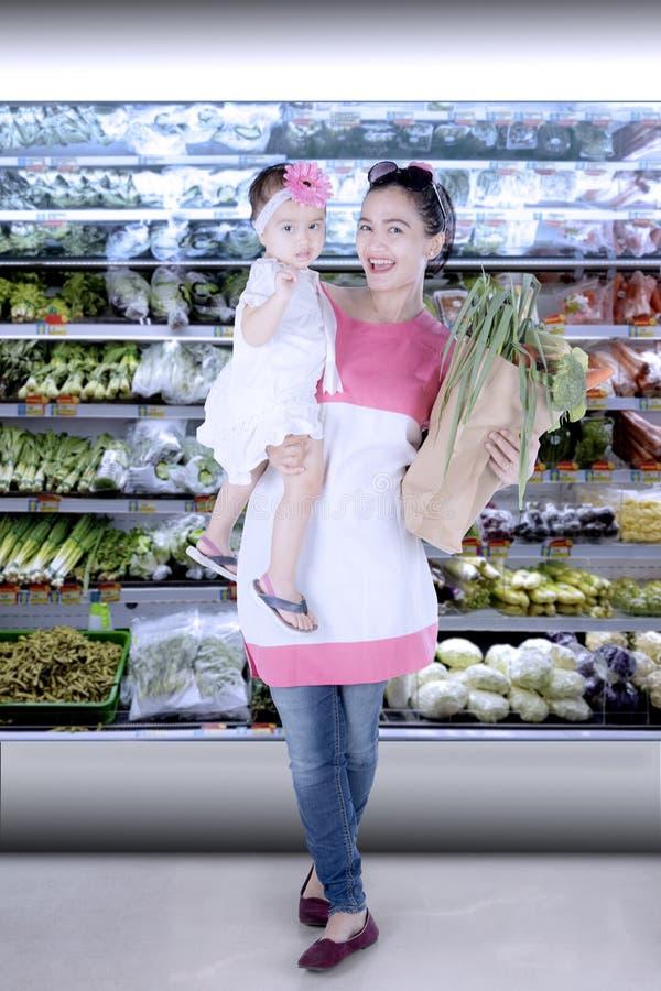Härlig moder med shoppingpåsen och barn arkivbilder