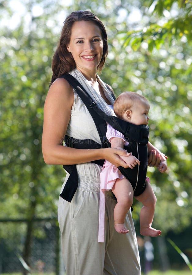 Härlig moder med spädbarnet i rem arkivbilder