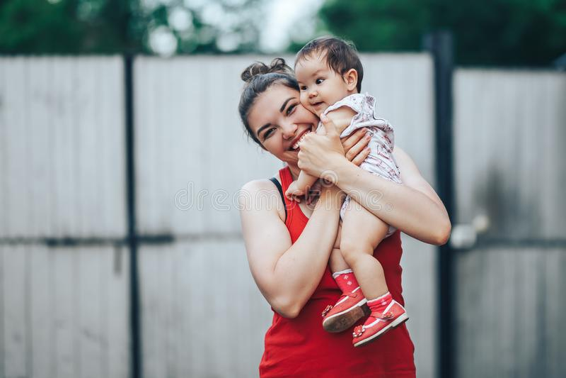 Härlig moder och att behandla som ett barn utomhus på gården av huset Skönhetmumen och hennes behandla som ett barn årigt spela f arkivbild