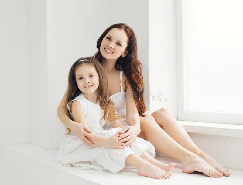Härlig moder och dotter hemma i vitt rum arkivfoto