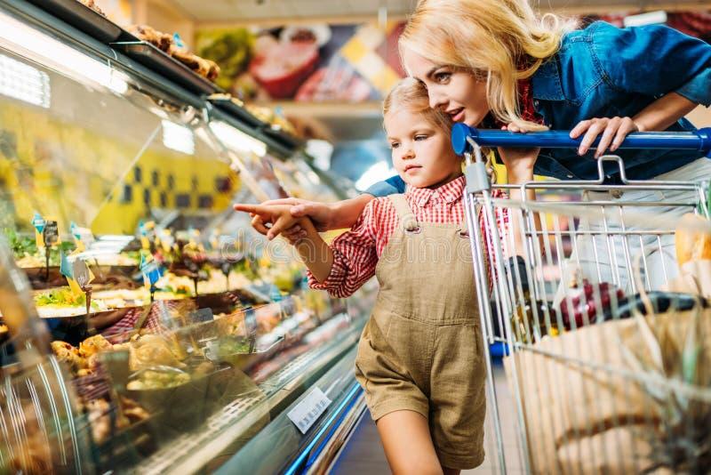 härlig moder och dotter med shoppingspårvagnen som väljer mat, medan shoppa royaltyfri bild