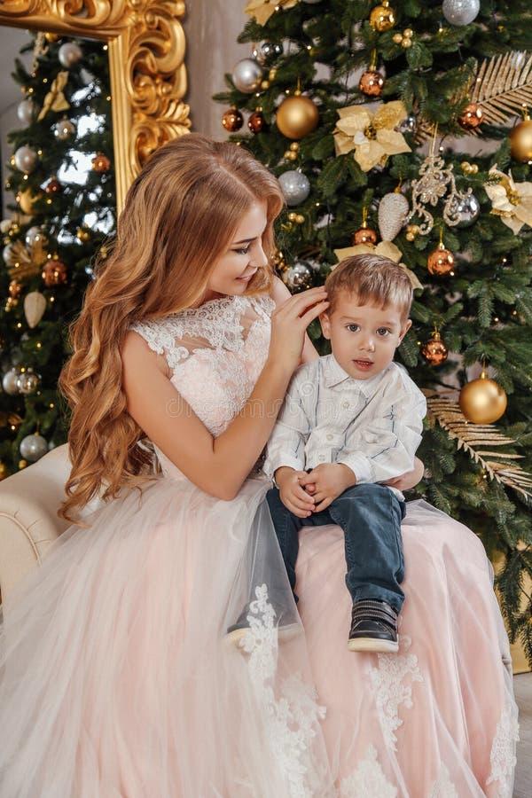 Härlig moder och hennes gullig liten son som poserar nära dekorerat träd för nytt år arkivfoton
