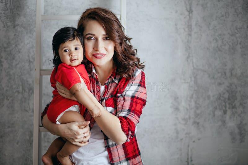 Härlig moder som rymmer hennes förtjusande lilla trevliga dotter royaltyfria bilder