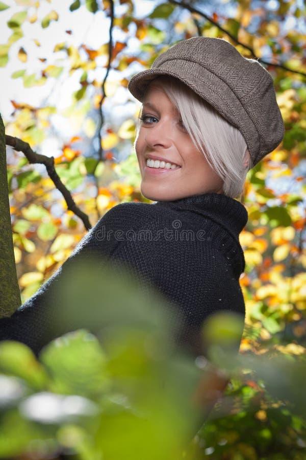 Härlig moderiktig kvinna i höstträd arkivbilder