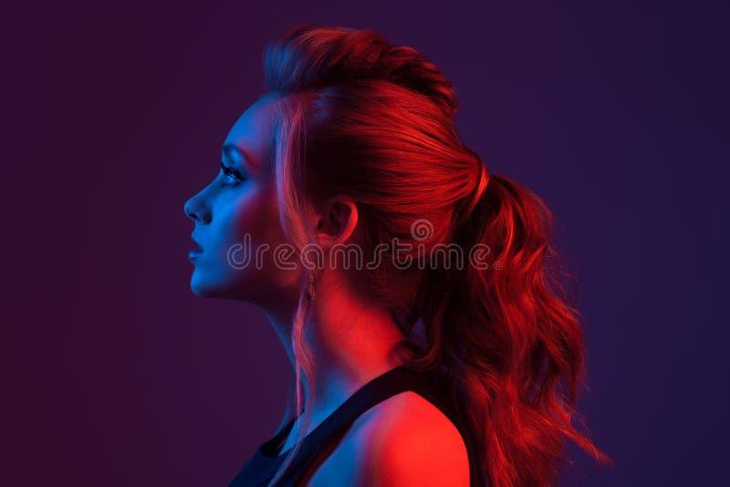 härlig modeståendekvinna frisyr Blå och röd li royaltyfri fotografi