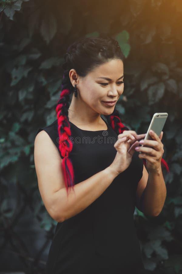 Härlig mogen asiatisk kvinnlig modell med utomhus- Smartphone royaltyfri foto