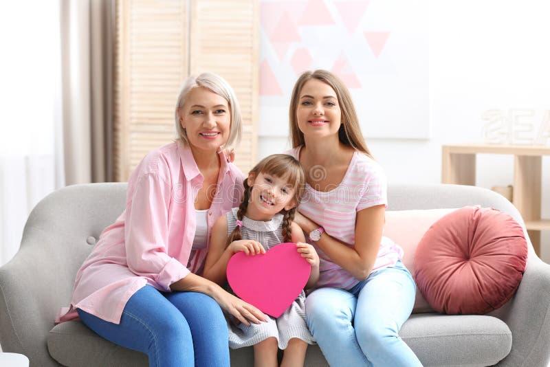 Härlig mogen dam, dotter och barnbarn med gåvan hemma Lycklig dag för kvinna` s arkivbild