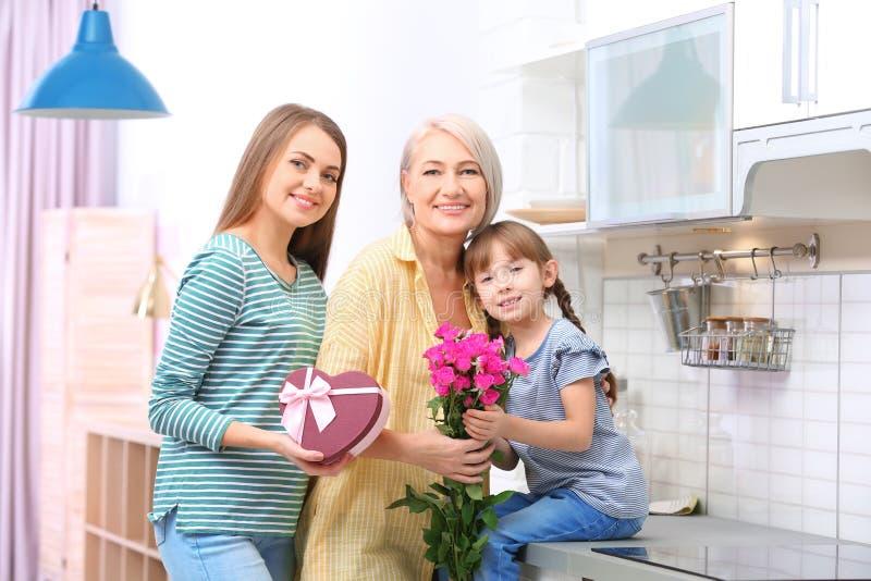 Härlig mogen dam, dotter och barnbarn med gåvor royaltyfri foto