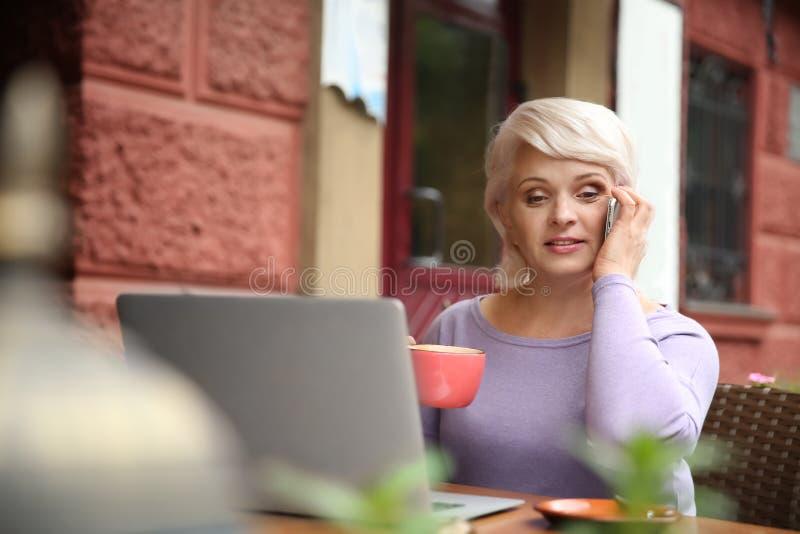 Härlig mogen kvinna med bärbara datorn som dricker kaffe och talar vid telefonen i kafé royaltyfri bild