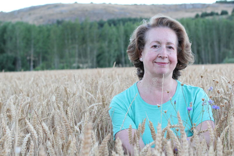 Härlig mogen kvinna med den långa iklädda väl till mods stilskjortan för krabbt hår som poserar i ett vetefält med serenitet arkivbild