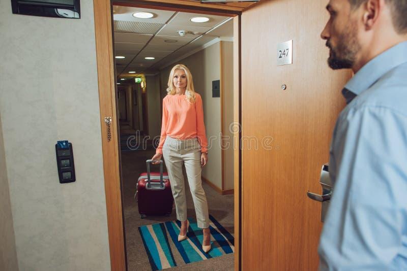 härlig mogen kvinna med resväskaanseende i hall medan skäggig manöppningsdörr royaltyfri bild