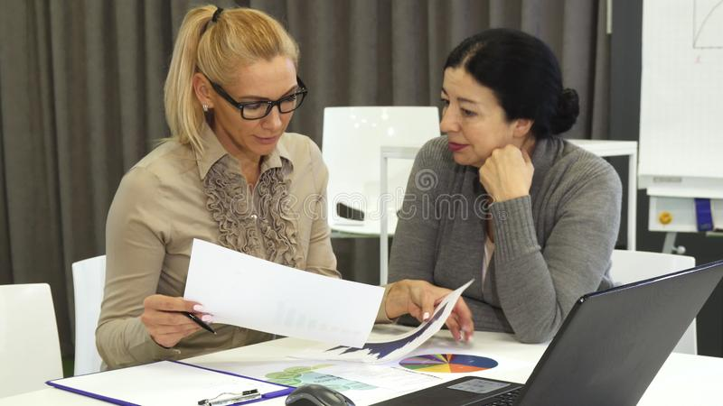 Härlig mogen kvinna och hennes höga affärscolelague på ett möte arkivfoto