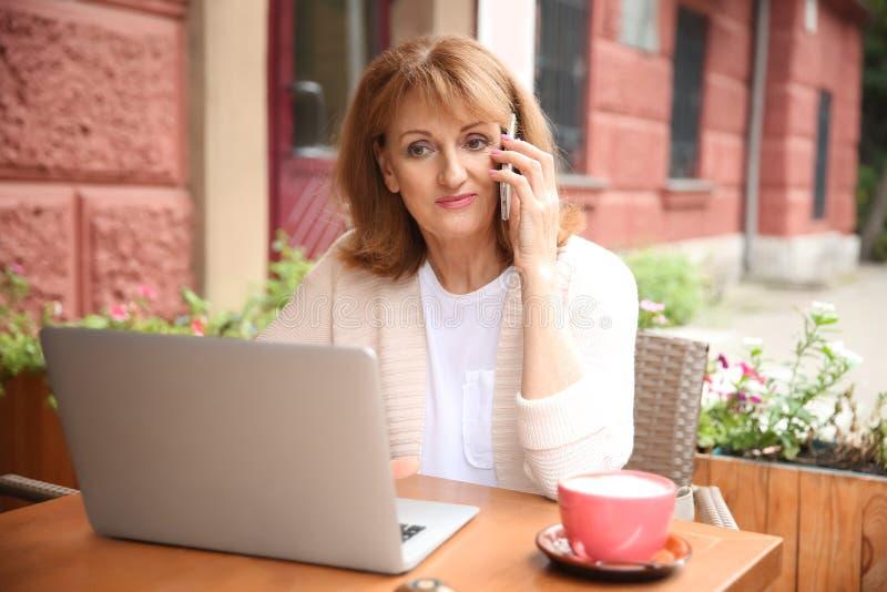 Härlig mogen kvinna som arbetar på bärbara datorn och talar vid telefonen i kafé royaltyfri fotografi