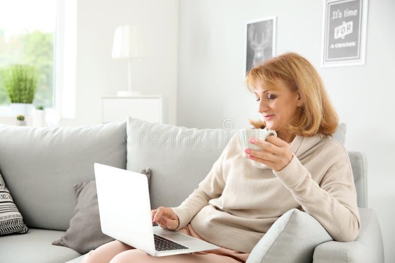 Härlig mogen kvinna som dricker kaffe, medan genom att använda bärbara datorn hemma royaltyfria foton